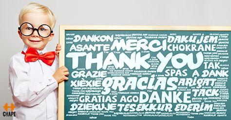 Danke steht in vielen Sprachen auf einer Tafel mit lächelndem Kind daneben