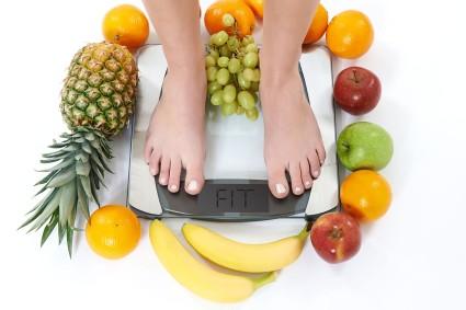 Frau auf Waage mit Obst