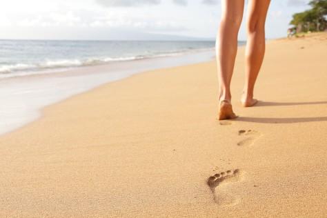 Beach travel - woman walking on sand beach closeup